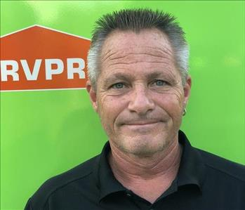 Male manager in front of green truck with orange SERVPRO logo