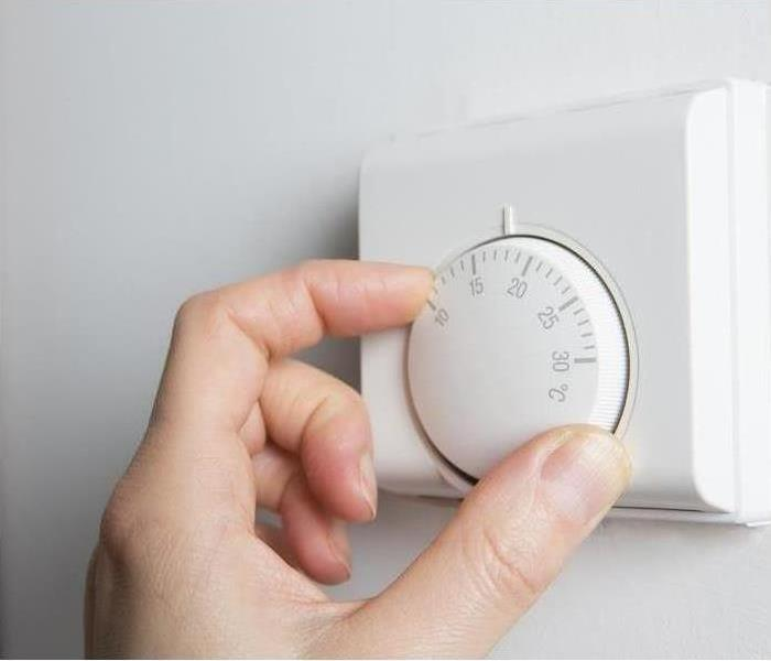 Hand adjusting the temperature on the wall thermostat